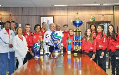 Prefeito Tuíze e secretário Carlinhos Bertagnolli, com a equipe de futsal feminino de Itu e as taças conquistadas.
